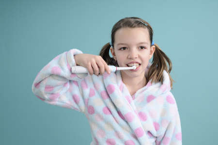 girl washing teeth in bathrobe photo