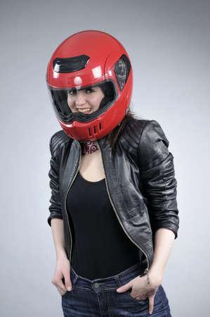 motociclista atractivo posando con casco rojo Foto de archivo