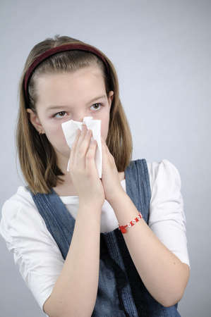 allergic girl blowing in tissue