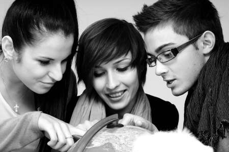 three students searching educational centres on globe photo