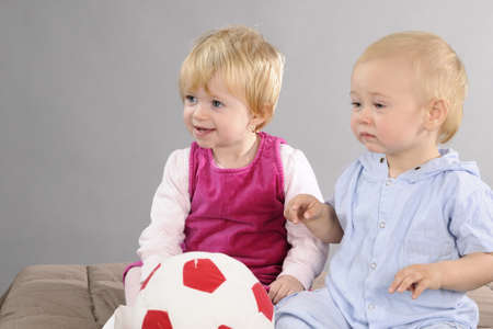 two babies playing with ball Stock Photo