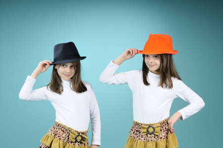ni�as gemelas: ni�as gemelas posando con sombrero