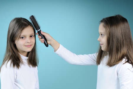 white twin girl arranging her sister hair with brush photo
