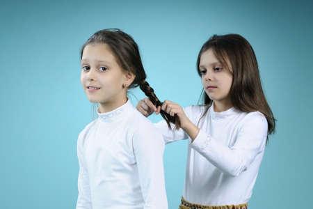cute twins creating braids