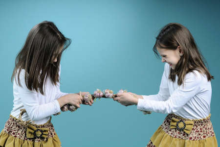 food fight: nervous twins fighting for garlic rope