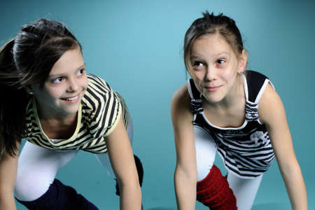 young gymnast twins exercising in studio photo