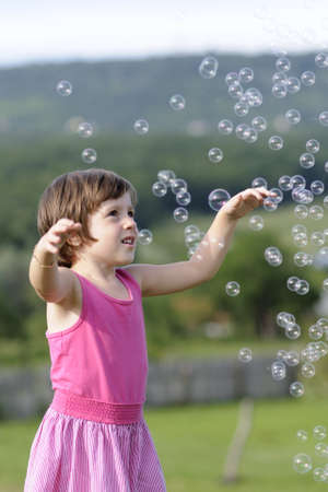 Happy kid catching bubbles Stock Photo
