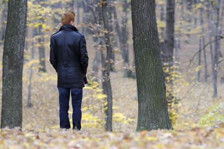 lonely person: back of sad man suffering in fall season