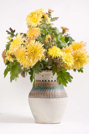 isolated beautiful yellow flowers in tradional vase photo