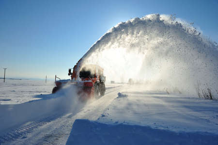 snow blower cleaning road in winter season photo