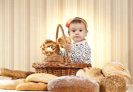 comiendo pan: ni�a comiendo pan de la cesta Foto de archivo