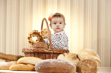 beautiful infant choosing bread form basket photo