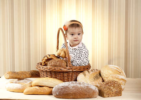 baby choosing bread from basket photo