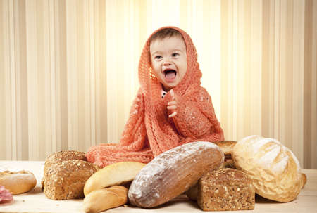 happy baby girl eating bread photo