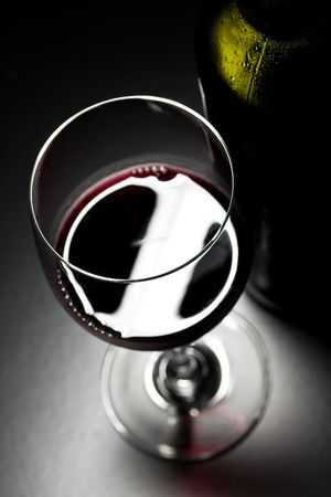 Wine glass and bottle in dark setting of a wine cellar