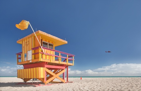 travel location: Miami Beach Florida, lifeguard house in typical colorful Art Deco style on a sunny summer day, with blue sky, and Atlantic Ocean in the background  World famous travel location