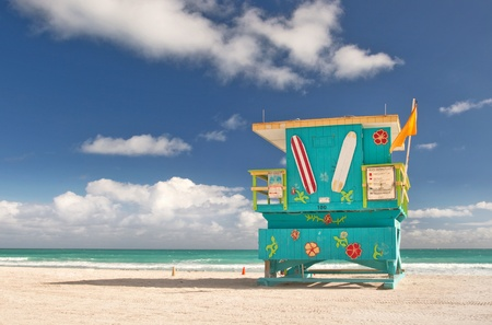 Miami Beach Florida, lifeguard house in typical colorful Art Deco style on a sunny summer day, with blue sky, and Atlantic Ocean in the background  World famous travel location