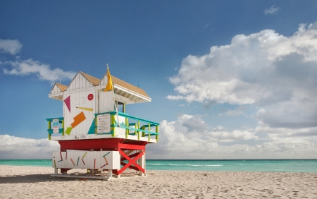 miami south beach: Miami Beach Florida, lifeguard house in typical colorful Art Deco style on a sunny summer day, with blue sky, and Atlantic Ocean in the background  World famous travel location