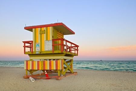Summer scene in Miami Beach Florida, with a colorful lifeguard house in a typical Art Deco architecture, at sunset with ocean and sky in the background   Stock Photo