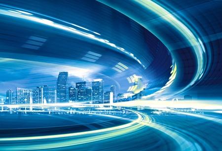 Ilustración abstracta de una carretera urbana que va hasta el moderno centro de la ciudad, la velocidad de movimiento con coloridas estelas de luz. Foto de archivo