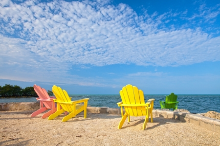 Summer scene with colorful lounge chairs on a tropical beach in Florida with palm tree and blue sky Stock Photo - 19428559
