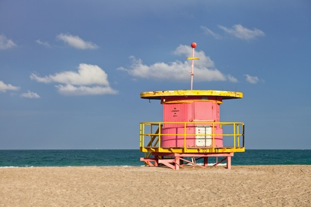 beach hut: Summer scene in Miami Beach Florida, with a colorful lifeguard house in a typical Art Deco architecture, with ocean and sky in the background.
