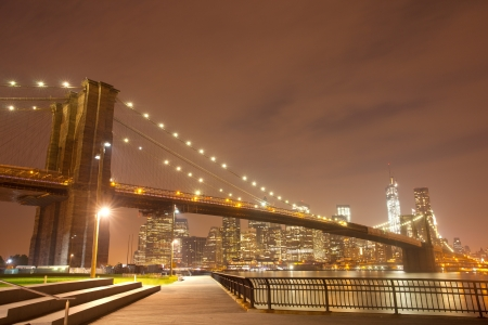 New York City night panorama with Brooklyn Bridge and illuminated downtown Manhattan business and residential buildings