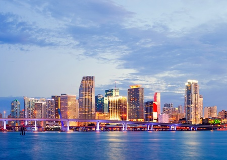 city of miami: CIty of Miami Florida, summer sunset panorama with colorful illuminated business and residential buildings and bridge on Biscayne Bay