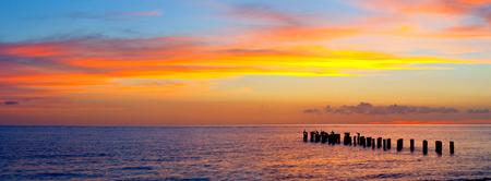 일출 또는 일몰 풍경, 아름다운 자연의 파노라마, 화려한, 빨강, 오렌지, 보라색 구름과 해변은 바다 물과 오래 된 부두의 컬럼에 반영. 나폴리 플로리