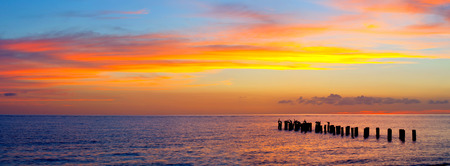 Sunset or sunrise landscape, panorama of beautiful nature, beach with colorful red, orange and purple clouds reflected in the ocean water and columns of an old pier. Taken in Naples Florida, USA.