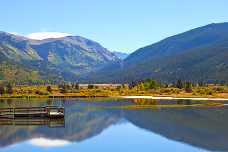 rocky mountains colorado: Landscape panorama of beautiful mountain nature and lake with reflections in Colorado USA on a sunny day with blue sky Stock Photo