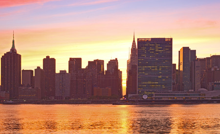 New York City, Manhattan famous landmark buildings skyline in downtown at beautiful colorful sunset with reflections