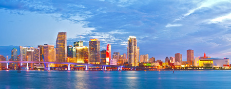 water's: Miami Florida at sunset, cityscape of modern downtown buildings illuminated with reflections in the waters of Biscayne BAy
