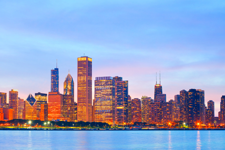 Cgicago Illinois skyline at sunset with illuminated downtown buildings