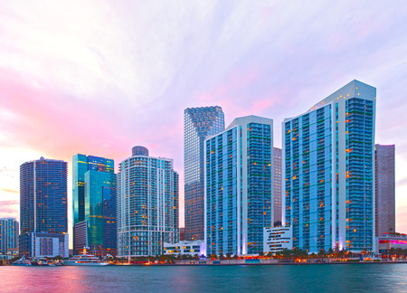 City of Miami Florida, night skyline. Cityscape of residential and business buildings illuminated at sunset with reflection