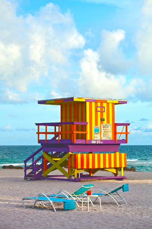 travel location: Miami Beach Florida, USA famous tropical travel location, typical Art Deco lifeguard house on a beautiful summer afternoon with ocean and blue sky