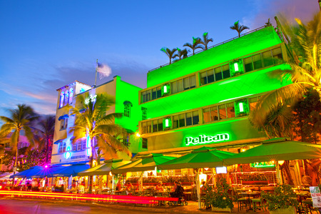 beach: Miami Beach, Florida USA-November 10, 2015: Moving traffic, Illuminated hotels and restaurants at sunset on Ocean Drive, world famous destination for nightlife, beautiful weather, Art Deco architecture and pristine beaches