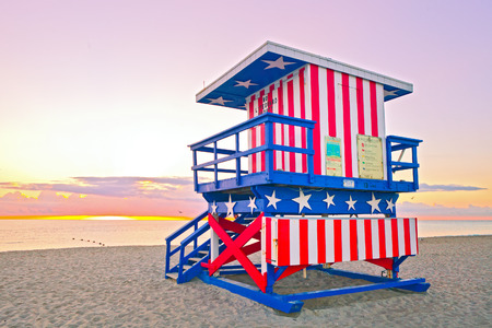 florida house: Sunrise in Miami Beach Florida, with a colorful American Flag lifeguard house in a typical Art Deco architecture, at sunrise with ocean and sky in the background.
