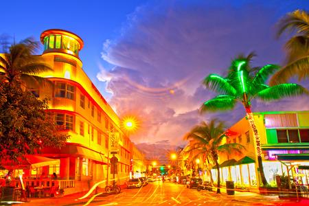 praia: Miami Beach, Florida 10 EUA-de novembro de 2015: Mudança de trânsito, hotéis e restaurantes iluminados ao pôr do sol na Ocean Drive, destino mundialmente famosa pela vida noturna, tempo bonito, arquitetura Art Deco e praias imaculadas Editorial