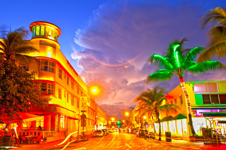 florida beach: Miami Beach, Florida USA-November 10, 2015: Moving traffic, Illuminated hotels and restaurants at sunset on Ocean Drive, world famous destination for nightlife, beautiful weather, Art Deco architecture and pristine beaches