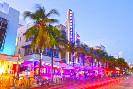 Miami Beach, Florida USA-November 10, 2015: Moving traffic, Illuminated hotels and restaurants at sunset on Ocean Drive, world famous destination for nightlife, beautiful weather, Art Deco architecture and pristine beaches