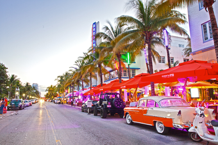 hotel resort: Miami Beach, Florida USA-November 10, 2015: Moving traffic, Illuminated hotels and restaurants at sunset on Ocean Drive, world famous destination for nightlife, beautiful weather, Art Deco architecture and pristine beaches