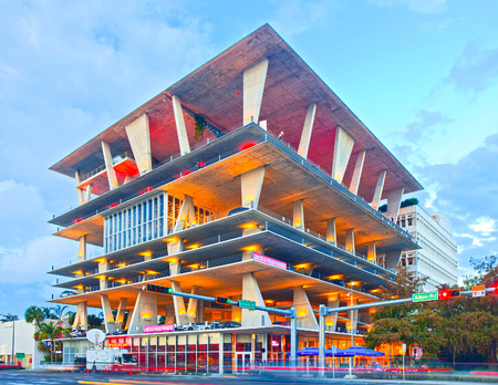 lincoln: Miami Beach, Florida USA-November 13, 2015:Mixed use building, designed by famous architects Herzog & de Meuron in Lincoln Road, Miami, FL, shops, dining and parking. Sunset shot with moving traffic Editorial