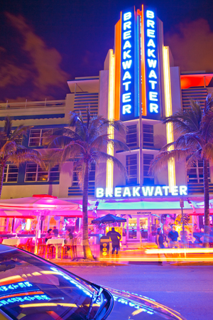 south beach: Miami Beach, Florida USA-November 9, 2015: Moving traffic, Illuminated Breakwater hotel with car reflection  and restaurants at sunset on Ocean Drive, world famous destination for nightlife, beautiful weather, Art Deco architecture and pristine beaches