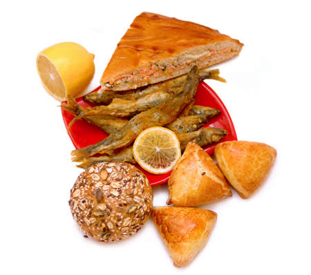 A piece of a fish pie, cakes with lemon, bread, fried fish on red original plate and lemon photo