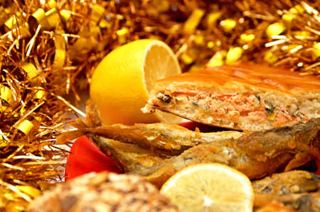 A piece of a fish pie, bread, fried fish on red original plate and lemon  Picturesque still life with a new year photo