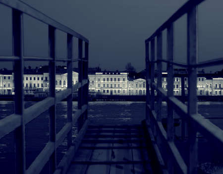 gangway: View of Neva and English embankment in St. Petersburg with night illumination through the gangway on pier, monochrome