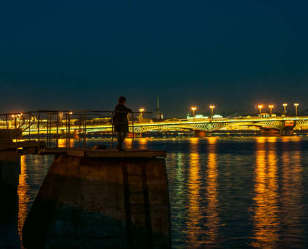 admires: Girl standing at night on city dock and admires romantic view of illumination city