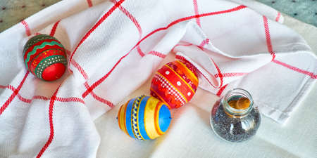 papiermache: Easter souvenir on kitchen table with checkered towel. Hand made Easter eggs from papier-mache and decorated with fabric and embroidery