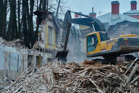dismantling: The demolition of building, excavator in work, destruction and ruins, dismantling of house
